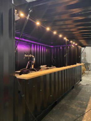 Event Festival container, een zwarte zee container in te zetten als tapcontainer, verkoopbalie, garderobe, infobalie, etc. voorzien van led verlichting en spots, 14 *220V stopcontacten en 32A aansluiting. Afmeting 6.00x2.50mtr 2 zijdeuren en 1 loopdeur aan de achterzijde.